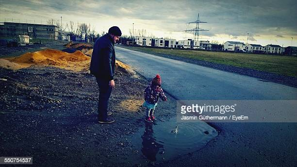 Father With Daughter Standing By Puddle