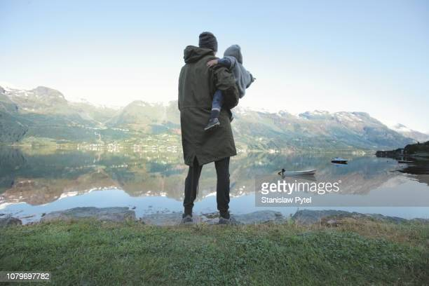 father with daughter standing on lakes edge - green coat stock pictures, royalty-free photos & images