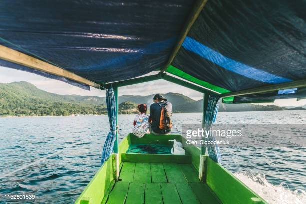 father with daughter traveling by boat on flores island - indonesian culture stock pictures, royalty-free photos & images