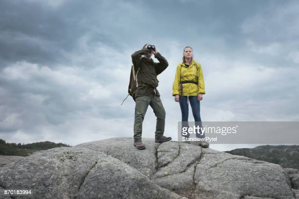 Father with daughter trekking in mountains, rainy weather