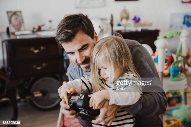 Father with daughter viewing images on back of camera