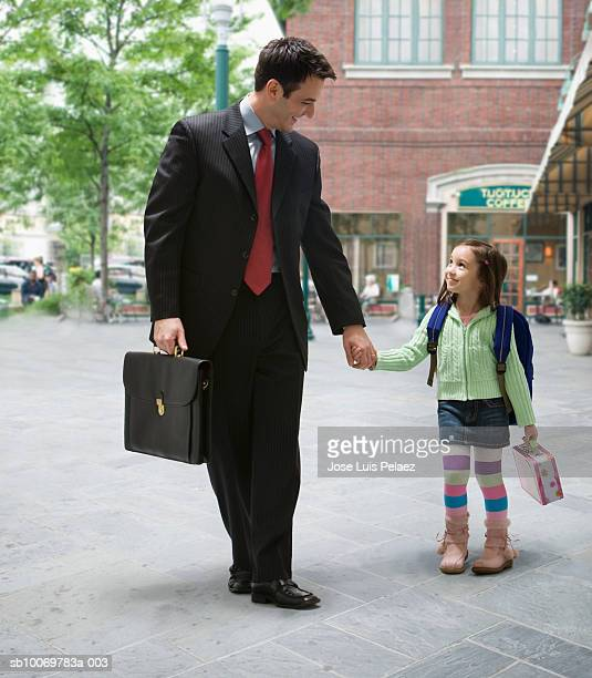 father with daughter (4-5) walking to school - genderblend stock-fotos und bilder