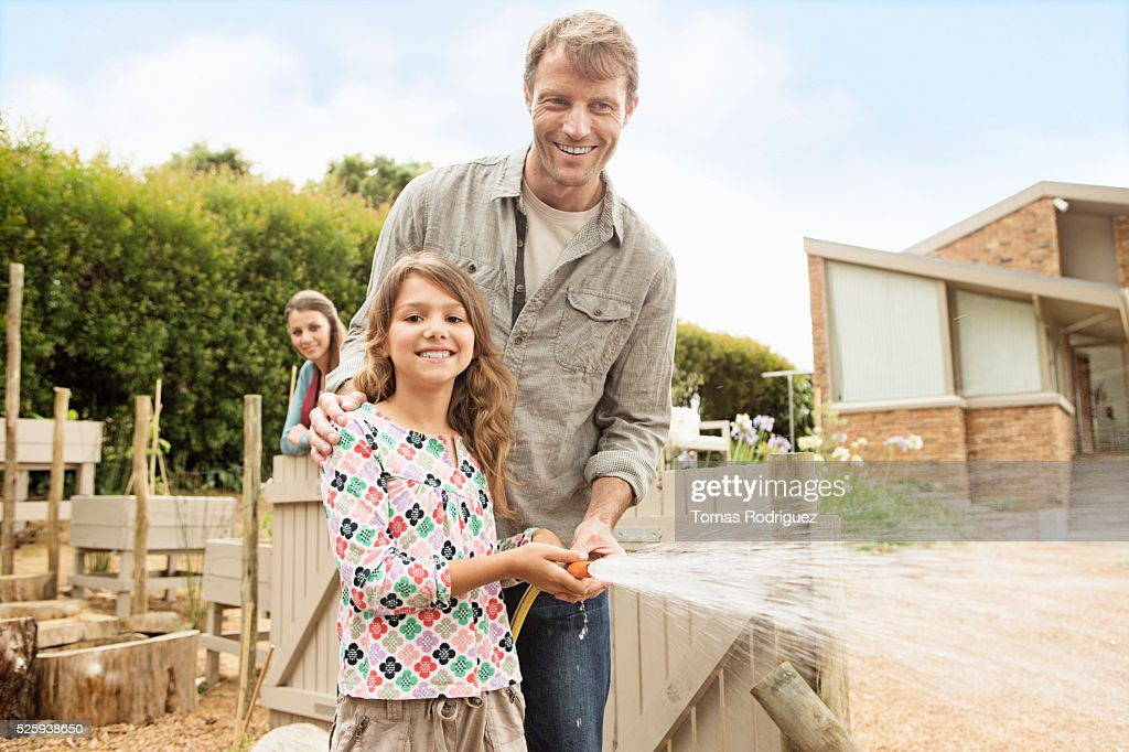 Father with daughter (8-9) watering vegetable garden : Stock Photo