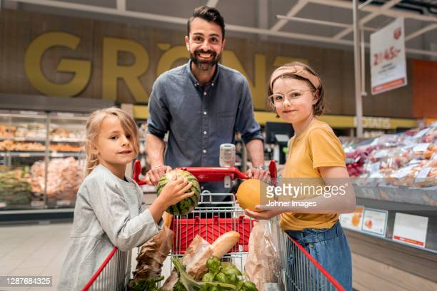 father with daughters doing shopping in supermarket - customer stock pictures, royalty-free photos & images