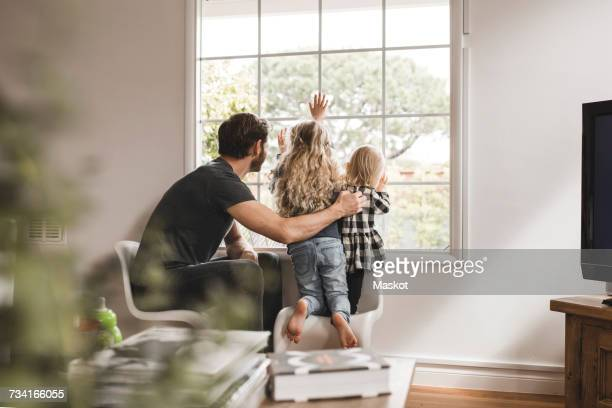 Father with daughters looking through window at home