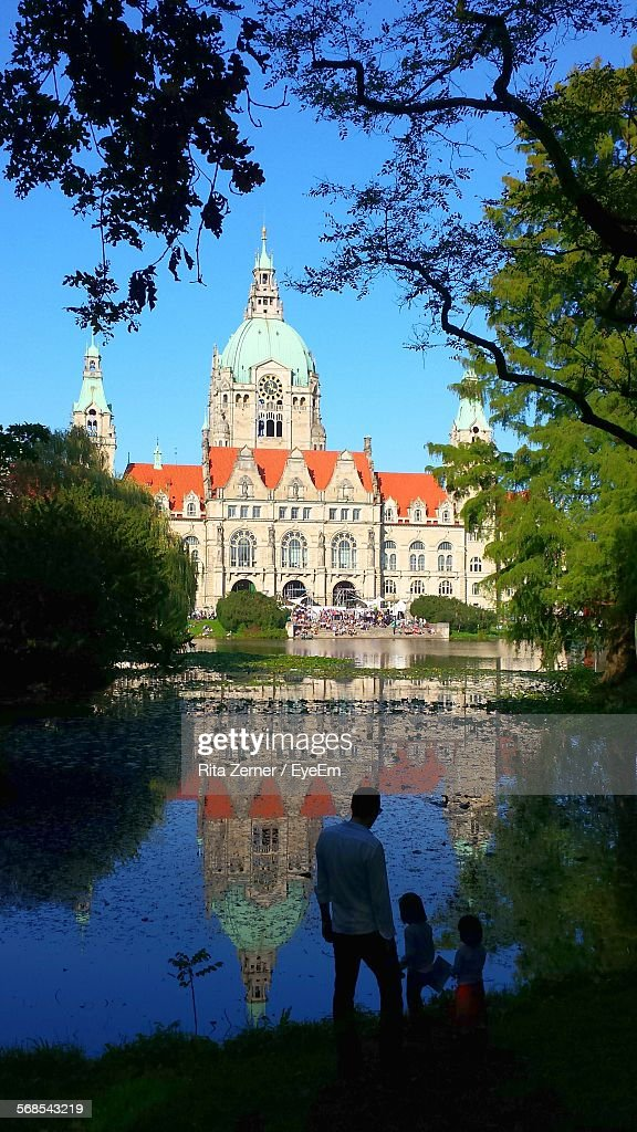 Father With Daughters Standing By New Town Hall Reflecting On Lake : Stock Photo