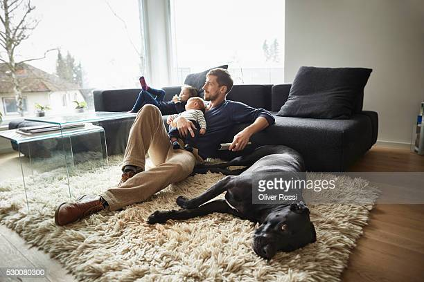 father with dog and two children relaxing in living room - genderblend stock-fotos und bilder
