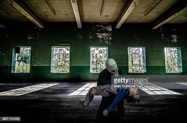 Father with gas mask holding dead son inside abandoned building