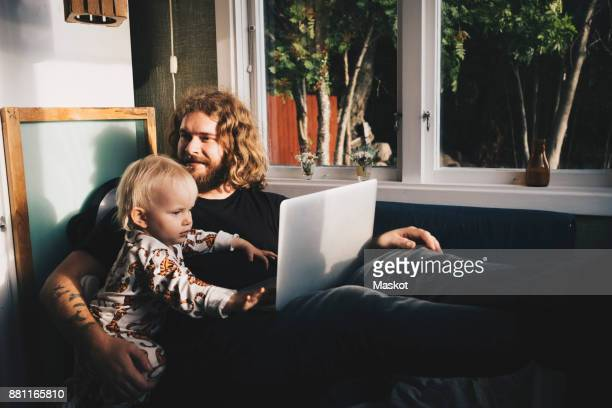 Father with girl holding laptop while sitting by window at home