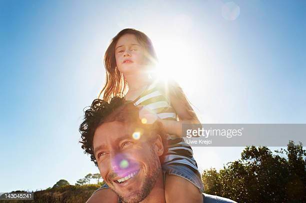 Father with girl (4 -6) on shoulders, outdoors