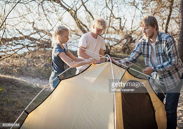 Father with his 2 children camping by the sea