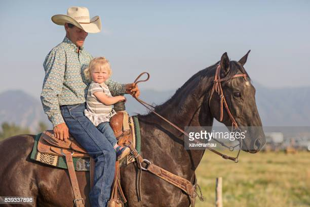 Father with his baby daughter having a great time horse riding