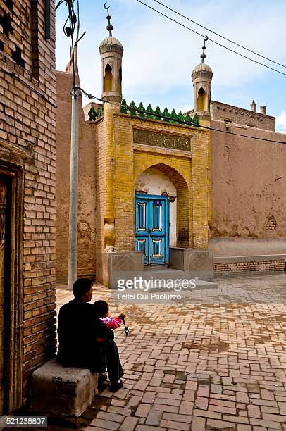a father with his baby sitting in front a mosque at old town kashgar, xinjiang province, china - kashgar stock photos and pictures