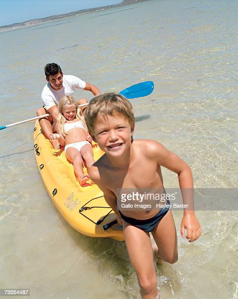 father with his children in a canoe in the sea - speedo boy stock photos and pictures