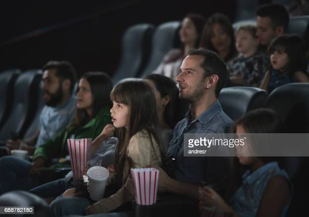 Father with his daughter watching a movie at the cinema