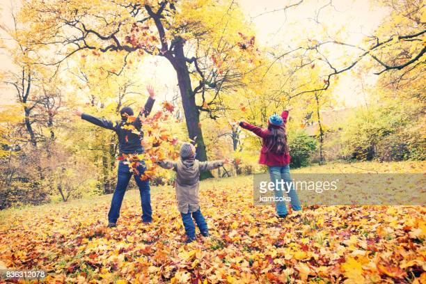 father with his daughters in autumn park - young leafs stock photos and pictures