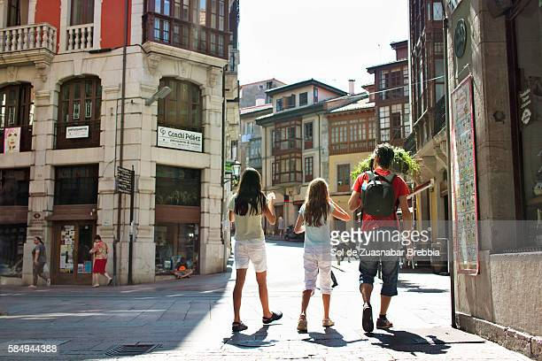 father with his girls walking the streets of llanes. spain. - llanes fotografías e imágenes de stock