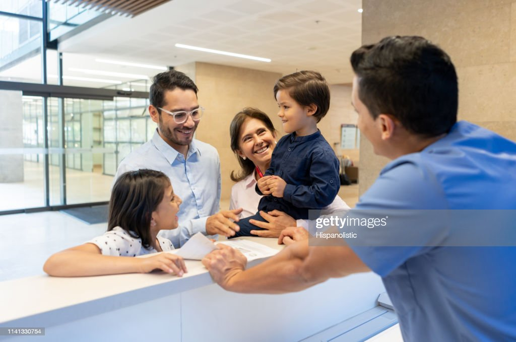 Father with his kids and grandmother registering before a consult with the pediatrician at the front desk of the clinic : Stock Photo