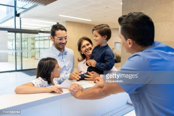 father with his kids and grandmother registering before a consult with the pediatrician at the front desk of the clinic - medical receptionist uniforms stock photos and pictures