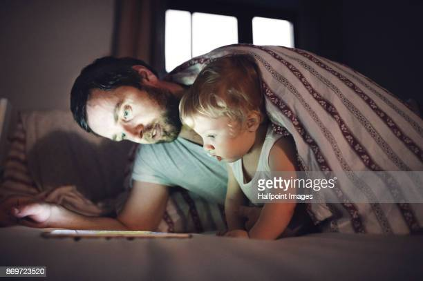 father with his son at home using tablet. - generation gap stock pictures, royalty-free photos & images