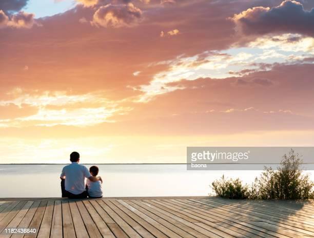 vader met zijn zoon genieten van het uitzicht op het meer - waterlijn stockfoto's en -beelden