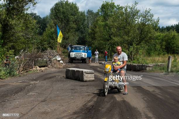 A father with his son seen riding on a motorbike at a Ukrainian checkpoint The conflict in the Donbass region of eastern Ukraine was started in early...