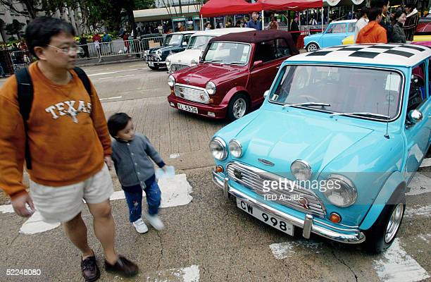 A father with his son walk past rows of British Mini Cooper cars parked along a street in central district of Hong Kong 27 February 2005 The cars...