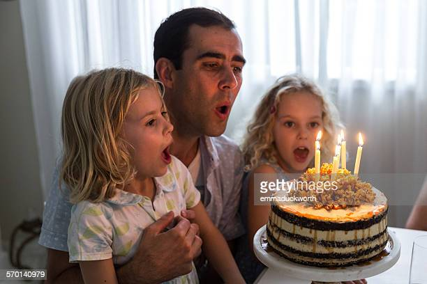 Father with his two daughters blowing out candles on birthday cake