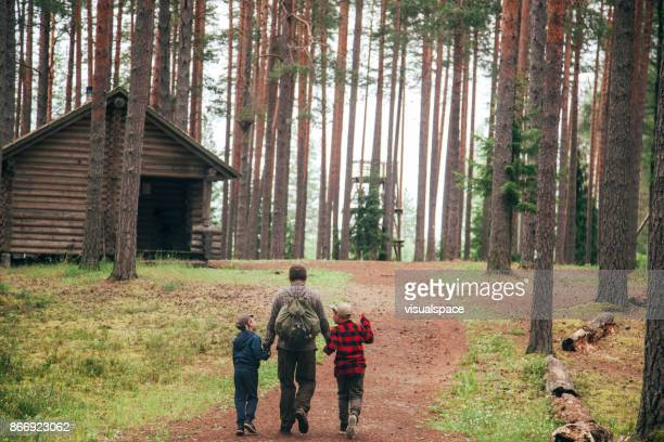 father with his two sons going to log cabin - log cabin stock pictures, royalty-free photos & images