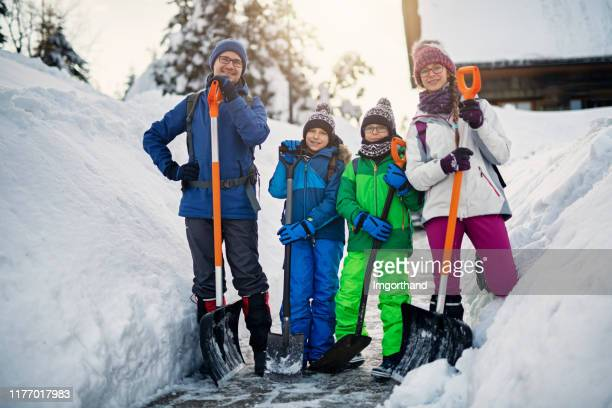 father with kids cleaning snow with shovels - digging stock pictures, royalty-free photos & images
