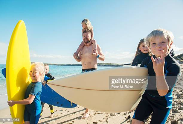Father with kids (4-7) having fun on beach with surfboards