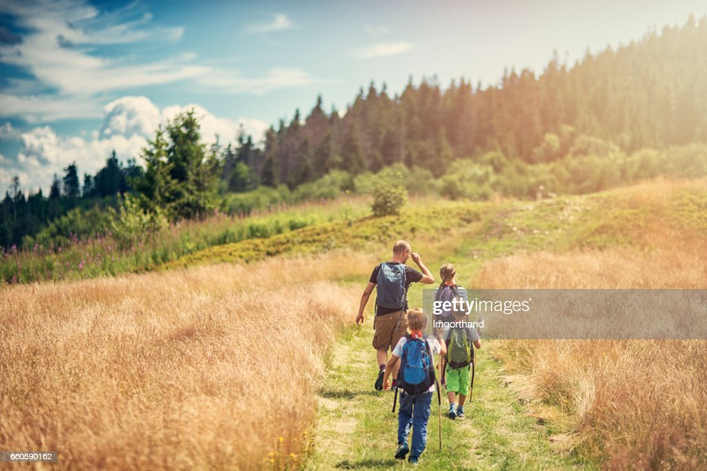 Father with kids hiking in beautiful nature : Stock Photo