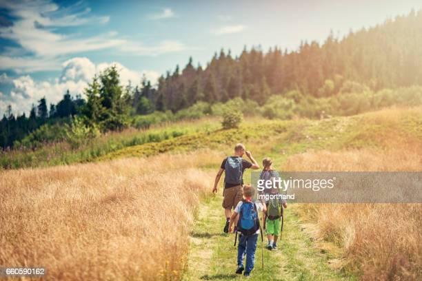 father with kids hiking in beautiful nature - backpacker stock pictures, royalty-free photos & images