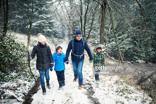 Father with kids hiking in beautiful winter forest