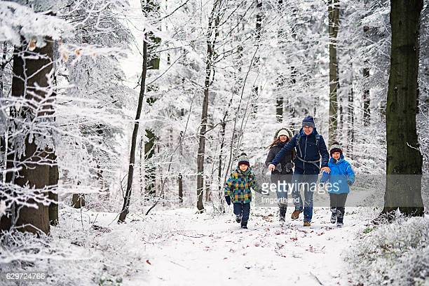 father with kids running in beautiful winter forest - winter weather stock photos and pictures