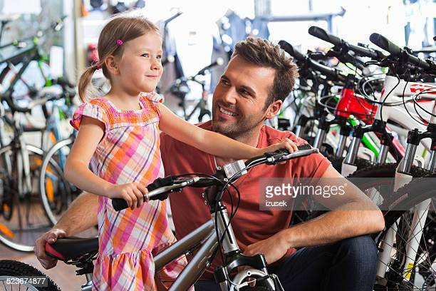 Father with little daughter in bike store