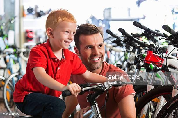 Père et petit fils à vélo magasin