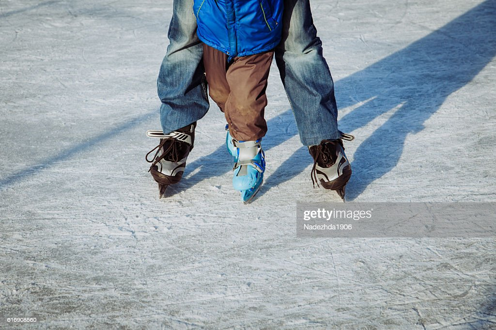 father with little son skating, family winter sport : Stock Photo