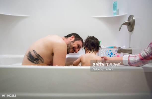 Father with loon tattoo smiling down at toddler while bathing together.