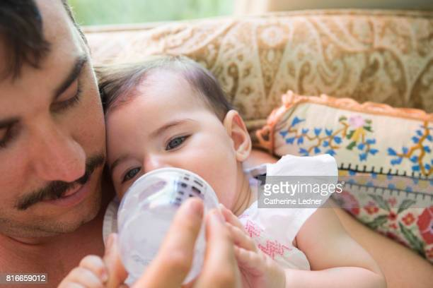 Father with mustache feeding baby a bottle
