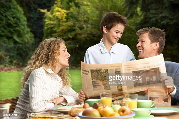 father with newspaper laughing with son (10-11 years), mother looking on, at breakfast - 30 34 years stock-fotos und bilder