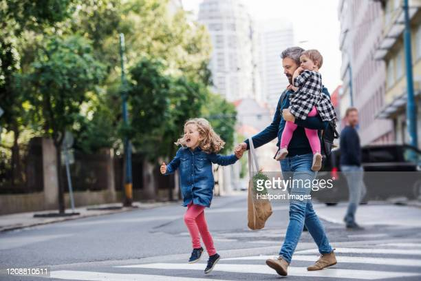 father with small girls walking outdoors in city, crossing the road. - pedestrian stock pictures, royalty-free photos & images