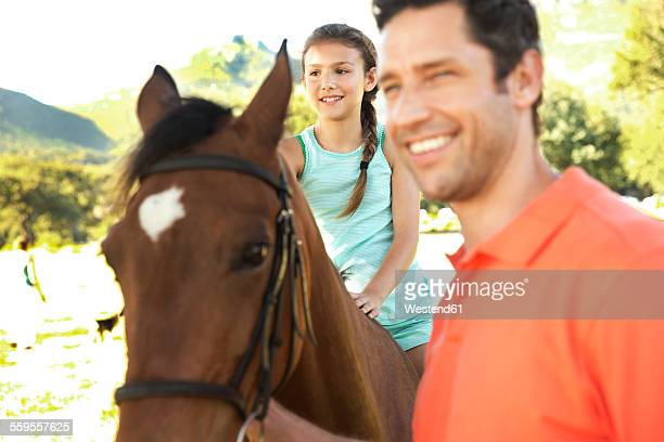 Father with smiling daughter sitting on horse
