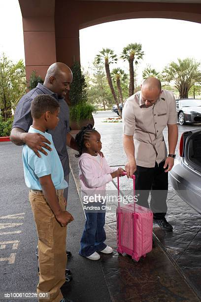 father with son (6-7 years) and daughter (4-5 years) being helped by bellhop on hotel driveway - 25 29 years stock pictures, royalty-free photos & images