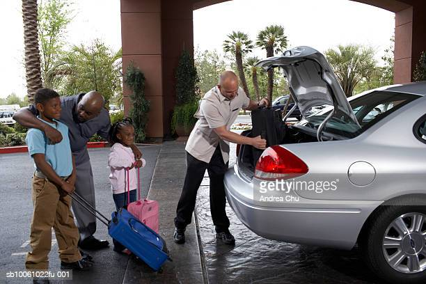 Father with son (6-7 years) and daughter (4-5 years) being helped by bellhop on hotel driveway