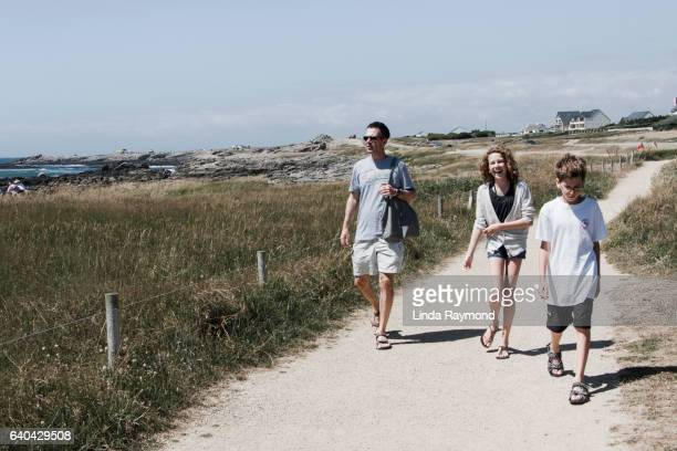 Father with son and daughter walking in a footpath