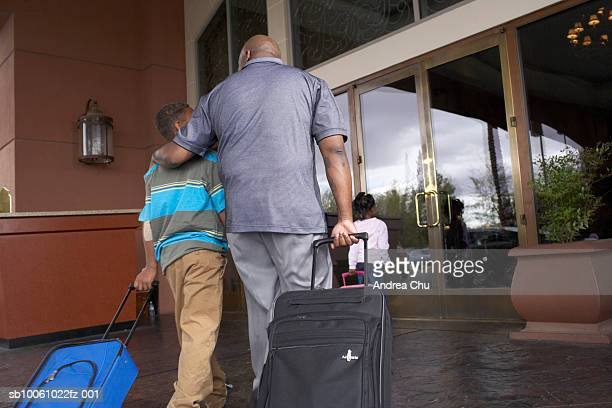 Father with son (6-7 years) and daughter (4-5 years) walking with suitcases towards hotel entrance door, rear view