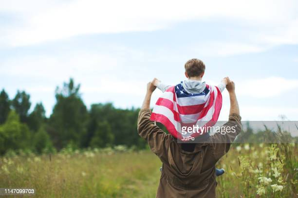 father with son celebrating independence day - fourth of july stock pictures, royalty-free photos & images