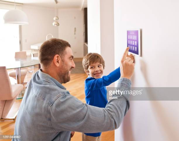 father with son controlling smart devices with a digital tablet at home - internet delle cose foto e immagini stock