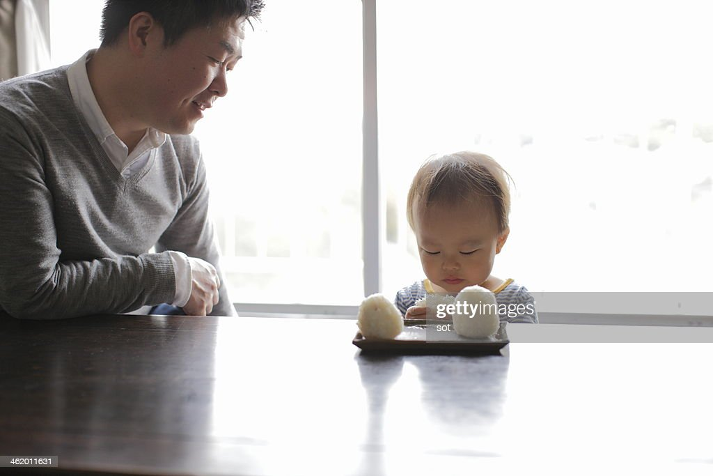 Father with son eating rice ball at table : Stock Photo